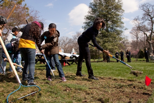 Mrs. Obama and the kids work on preparing the soil for the garden.